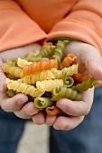 Child's hands holding coloured spiral pasta
