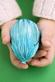 Child's hands holding Easter egg in blue foil