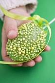 Child's hand holding green decorated Easter egg