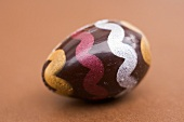 Painted chocolate egg on brown background