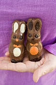 Hand holding two chocolate Easter Bunnies