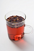 Fruit tea with tea leaves in glass cup