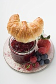 Berry jam, croissant and fresh berries on plate