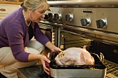 Woman putting stuffed turkey into the oven
