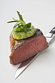 Beef steak with herb butter on knife (showing cut edge)