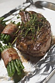 Beef steak with bacon-wrapped beans on aluminium foil