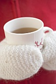 Hands in mittens holding cup of hot tea