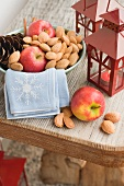 Red apples, almonds and cone in bowl, lanterns beside it
