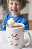 Cup of cocoa with marshmallow, small boy in background