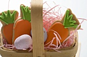 Easter biscuits (carrots) and sugar eggs in basket