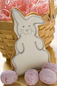 Easter biscuit (Easter Bunny) & sugar eggs in front of basket