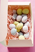 Pastel-coloured sugar eggs in pink box