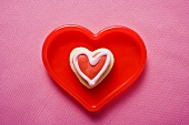 Heart-shaped iced biscuit in red dish