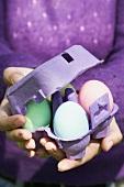 Woman holding egg box full of coloured eggs