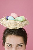 Woman carrying basket of coloured eggs on her head