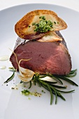 Roast fillet of beef with vegetable crisps, rosemary, garlic