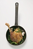 Fried goose leg with rosemary in frying pan (overhead view)