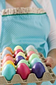 Woman holding egg tray full of coloured Easter eggs