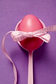 Red Easter egg with bow on spoon (overhead view)