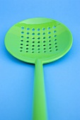 Green slotted spoon on blue background