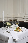 Salad and white wine on laid table in restaurant