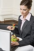 Woman with laptop eating salad in restaurant