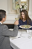 Couple clinking glasses of white wine in restaurant
