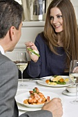 Woman offering man asparagus on fork in restaurant