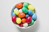 Coloured sugar eggs in white dish