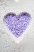 Purple sugar in heart-shaped biscuit mould