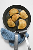 Breaded pasties in frying pan with spatula (overhead view)