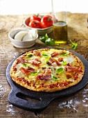 Tomato, mozzarella and ham pizza with basil