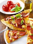 Slice of pepperoni pizza with basil on server