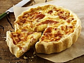 Quiche Lorraine, a slice cut, on baking parchment