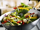 Mixed vegetables in wok and on spatula
