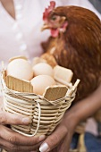 Woman holding live hen and basket of eggs