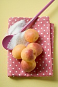 Apricots on tea towel, cooking spoon and sugar