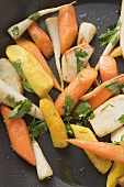 Fried root vegetables with parsley in frying pan