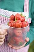 Child holding measuring jug full of strawberries