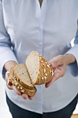 Woman holding partly sliced loaf of oat bread