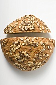 Wholemeal bread with pumpkin seeds, cut in two