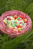 Easter nest full of coloured sugar eggs in grass