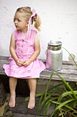 Small girl on wooden bench beside milk can