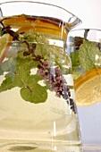 Herbal drink with slices of lemon in glass jug