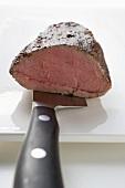 Roast beef fillet on knife