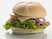 Bread roll filled with ham, cheese, lettuce and tomato