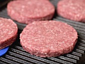 Raw burgers on electric grill