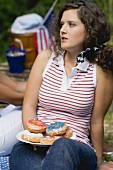 Young woman holding plate of doughnuts on the 4th of July (USA)