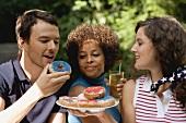 Junge Leute mit Doughnuts und Eistee beim 4th of July (USA)