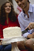 Man cutting coconut cake (4th of July, USA)